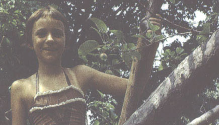 BetsyAge11: Betsy Devine with big smile in apple tree, age 11.